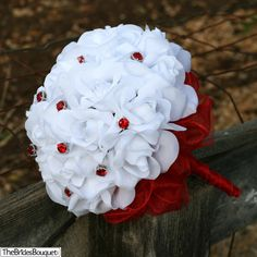 This is the Snow White Silk Rose Hand Tied bouquet with 2 dozen roses and 12 red bouquet jewels. TheBridesBouquet.com
