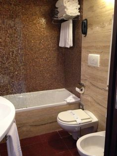 Bathroom in Roma, Italy. All materials can be purchased at Floor & Decor. Brown mix mosaic is only $3.99/sqft. You can either use marble or polished travertine 12x24 on walls! GORG.