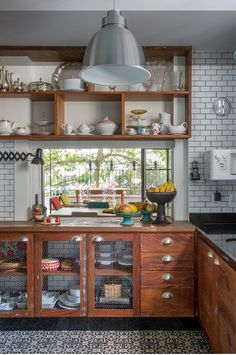 Love the cabinets going clear to the ceiling. The window/opening into the next room. Wood tones with the subway tile. Amazing.