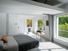 Leap Into the Year of the Dog With These 25 Pups in the Modern World - Photo 2 of 25 - In the master bedroom, a Droog Milk Bottle lamp hangs next to a Fluttua Bed designed by Daniele Lago. An artwork by Brooke Westlund hangs over a custom pet door for the client's dog, Kona.