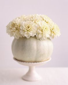 White Pumpkin Flower Arrangment - A white pumpkin is transformed into a homemade vase. Select a pumpkin about eight inches in diameter; cut off the top, and scoop out pulp and seeds. Place a small container, such as a highball glass, inside the pumpkin. Trim flowers to fit (we used twelve dahlias, but two dozen carnations would also work), and arrange in the glass.