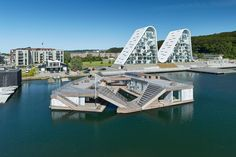 The Floating Kayak Club is located on the water pulled away from the shore, which highlights the building as a sculptural object and focuses on kayaking as an outdoor water sport. As the building floats, the relationship between the building and the w