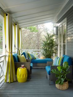 A narrow porch can make for a surprisingly accommodating outdoor room, as evidenced by our Idea Cottage in Seagrove, Florida. Designer Paige Schnell incorporated a playful palette of teal and yellow (we love the striped curtains with nautical rope ties) f