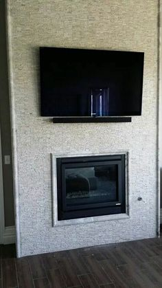 """55"""" Sony LED Smart TV with sound bar mounted over fireplace in master bedroom"""