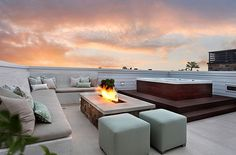 rooftop space with modern couch, outdoor fireplace and jacuzzi