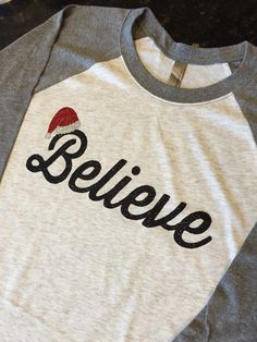 Believe santa claus hat Baseball Raglan Tee. Christmas Shirts for Women. Christmas Clothes. by MintElephantTeeCo on Etsy https://www.etsy.com/listing/259988692/believe-santa-claus-hat-baseball-raglan