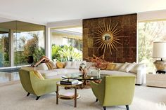 A sunburst mirror from JF Chen accents a wall of mica tile in photographer Steven Meisel's Los Angeles living room, decorated by Brad Dunning; the chairs are by Michael Berman, and the driftwood-and-glass table and curved Monteverdi-Young sofa are original to the house.