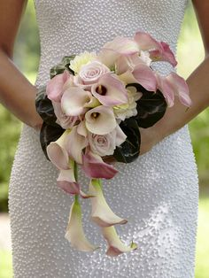 A simple yet incredibly beautiful bouquet, which exudes pure elegance and feminine charm. Pale pink mini calla lilies, roses and dahlias are arranged in a cascade style and accented with a white taffeta ribbon to create an unforgettable look.