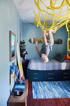 This boy& bedroom is bright and full of fun with surfboards and skateboards all over the place – but what is that on the ceiling? A yellow net is attached for climbing, flipping, and general fun. What a cool idea for those busy kids who like to climb! Master Bedroom Closet, Girls Bedroom, Trendy Bedroom, 4 Year Old Boy Bedroom, Diy Bedroom, Teen Boy Rooms, Bedroom Beach, Bedroom Wall, Bedroom Storage
