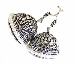 Oxidized Black Metal Jhumkas/Jhumkis with Pearls:With an intricate craved pattern and studded with pretty little pearls, the pair ticks all the boxes for an