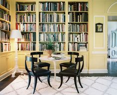 A tulip table and black klismos chairs surrounded by yellow built-in bookshelves.