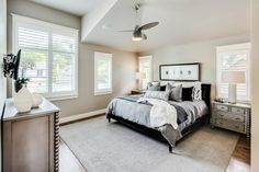 Flanked by matching nightstands and contemporary white lamps, the sleek black bed takes center stage and is dressed in luxurious gray linens. The dresser echos the look of the nightstands with distressed wood and ball-turned details.