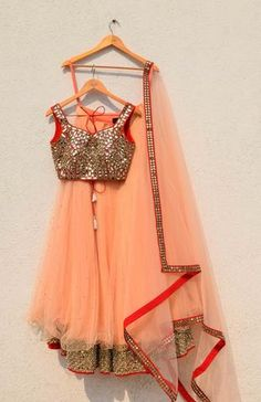Uber feminine and Flirty- The Peach Lehenga with red mirror blouse and mirror work border at the bottom is one of our bestsellers with the Indian fashioni Choli Designs, Lehenga Designs, Dress Designs, Indian Wedding Outfits, Indian Outfits, Indian Clothes, Indian Weddings, Indian Attire, Indian Wear
