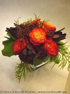 Circus Roses, Seasonal Berries and Leucadendron housed in a square vase with an exotic leaf wrapped inside.