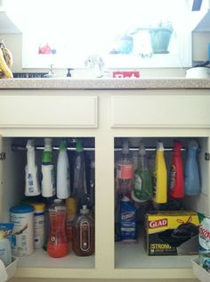 Hanging spray bottles by a tension rod under the sink to save room! Great idea!