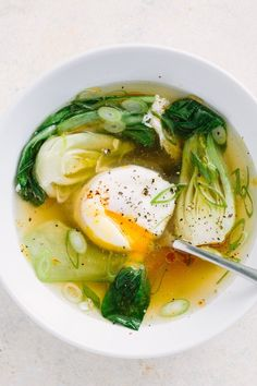 This Gingery Poached Egg Soup Recipe Takes Just 15 Minutes to Make! This FAST HEALTHY and EASY soup is simple. Great lunch or dinner for a family - or one. Low calories, low carb, gluten free and vegetarian! You'll need sesame oil, vegetable broth or chicken stock, ginger, garlic, soy sauce or tamari, bok choy or napa cabbage, eggs, and scallions. Perfect cold weather cooking or if you're looking for food to eat to make you feel better when you're sick with the flu or a sore throat!