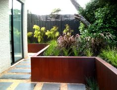 Lump Sculpture Studio specializing in Corten Steel: Corten Steel Cladding placed over the top of timber retaining walls