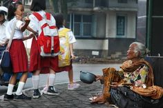 """Dian Agung Nugroho's photo """"F*** You (What's on her mind ?)"""" captures a Chinese schoolgirl flipping off an old Chinese beggar lady. The title really asks the important question -- what does this little girl know, and what has she been told, that has led her to this pass?"""