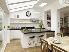 Metro matt white lacquer bespoke kitchen in contemporary style by Roundhouse. A small side return extension can bring so much extra space to your kitchen.