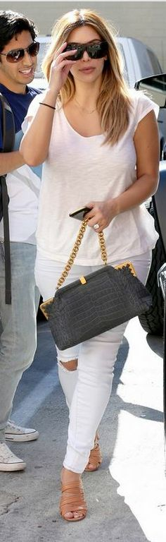 Who made  Kim Kardashian's sunglasses, gray chain handbag and tan sandals?