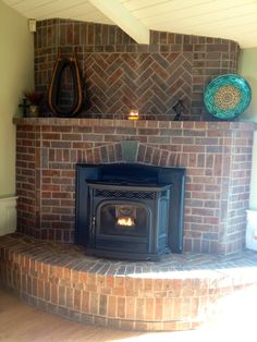 Brick fireplace.  Corner placement, red brick, herringbone detail, vertical brick placements.