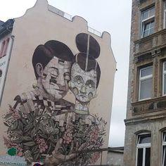 Foto de uma parede lateral de um prédio na Alemanha com um grafite de Pixel Pancho, muralista italiano, de Turim. Pancho mistura o orgânico-mecânico com exatidão nos traços e uma sutil fantasia. Descrição: Parede em fundo bege, ao centro, um casal da cin