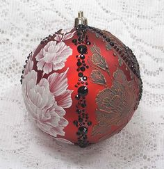 Margot Clark created this red, double design ornament with a 3D texture painted MUD design of roses (white on one side and copper metallic on the other side) and added black rhinestone bling. Each ornament created is a one-of-a-kind. The texture medium and paint brush used to paint the ornaments were both created to my specifications. Gift boxed. Ornament weight is 2 ounces. My signature M is located on the bottom of the ornament. Measures 3 1/2 x 3 1/2