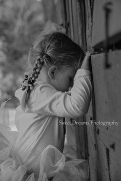 Outdoor black and white birthday session, 3 year old little girl looking in a barn  www.facebook,com/sweetdphotos