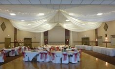 Ivory Ceiling Drape, White Chair Covers with Apple Red Organza Sashes (traditional bow) at Brooklyn Park Community Center by Deckci Decor