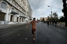 Athens, Greece: a naked demonstrator flashes the victory sign during a demonstration against a visit by the German chancellor, Angela MerkelPhotograph: Aris Messinis/AFP/Getty Images