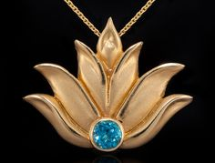 "This lotus flower pendant necklace is 14k yellow gold with a blue topaz stone. It has a hidden bail which allows for it to fall simply and beautifully on the neck. It measures approximately 1"" x 1"" and comes with an adjustable 16- 22"" coordinating cable chain. This piece also comes in a 1/2"" size. Please check other listings for details."