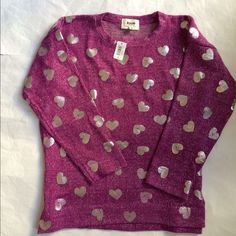 """Girls Over-Sized Silver Foil Heart Sweater 76% polyester/ 24% rayon.  A grapish-magenta color with silver hearts. Sweater width is 18-1/2"""" across the top of shoulders. 18"""" right under the armpit to armpit. Length from back of neck to hem 22"""".  Size Large 12/14  NWT open to offers. American Kids Wear Sweaters"""