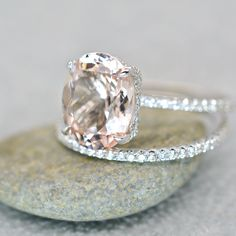 This stunning 3.40 ct. morganite and diamond engagement ring will sweep her off her feet. Bright and beautiful center stone is eye clean. Simple white gold shank encrusted with diamonds. Beautiful oval cut morganite grasped with diamond set prongs. This listing is for the engagement ring only, message us if you are interested in the matching band! Unique & breathtaking. Center Stone: Morganite Weight: 3.00 ct. Color: Peachy pink Clarity: VS absolutely eye clean Shape: Oval Side Stones…