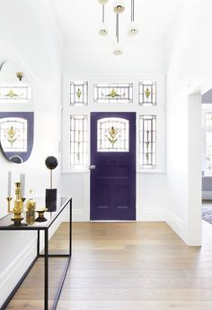 A purple front door makes for a grand entryway at this Edwardian style home complete with period details including stunning stained glass windows | Photography: Armelle Habib | Styling: Heather Nette King