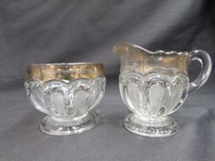 "Antique EAPG US Glass Loops with Stippled Panels Creamer and Sugar Set.  This set was made around 1900 by U.S. Glass Company.  The akal name is Loops with Stippled Panels.  Texas is the pattern name.  This set originally had the gold around the tops but the majority of the gold is worn off.  The creamer is approx. 3"" tall x 4"" from spout to handle.  The sugar bowl is approx. 3 1/8"" across x 2 5/8"" tall.  There is wear to the bottoms and the gold.  The seams and points of the scallop are ..."