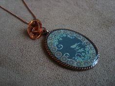 Colar em corrente e rosa de metal na cor cobre. Pingente em base de metal cobre com aplicação de imagem de flores e passarinho. R$38,00