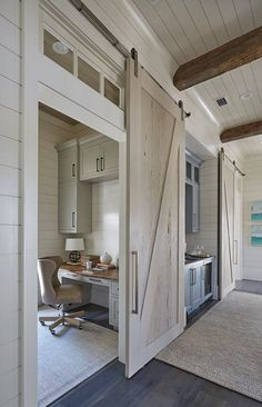 One of the pecky cypress barn door opens to reveal a home office with light gray cabinets suspended over a gray built-in desk with wood top. Barn doors are painted in a custom whitewash stain.