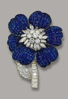 A SAPPHIRE AND DIAMOND FLOWER BROOCH, BY CARTIER The vari-cut diamond cluster centre set en tremblant, within the calibré-cut sapphire petals to the graduated baguette-cut diamond stem and brilliant-cut diamond leaf (two sapphires deficient), circa 1960, 7.0 cm. high, with French assay marks for platinum and gold, in red leather Cartier case Signed Cartier OCC, No. 1655