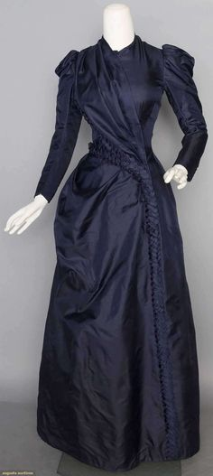 "NAVY SILK DAY DRESS, c. 1888 1-piece, soft silk twill, cross-over bodice w/ chenille yarn & navy silk ribbon tabs, princess back seams, cotton linings, B 31"", W 21"", L 57""-60"""