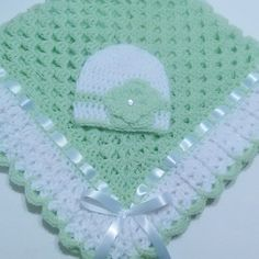 """This beautiful hand crocheted granny square baby blanket is made of 100% baby soft yarn. It is made out of a very good high quality yarn.  Very soft and colorful blanket set.  Beautiful hand crochet baby blanket and baby beanie hat in light green and white colors. White satin ribbon woven in edge of blanket.   Beanie hat has a beautiful crocheted flower and flat pearl button.  Makes an EXCELLENT baby shower GIFT!  It measures at about 34"""" inches by 34"""" inches square...perfect stroller, car…"""