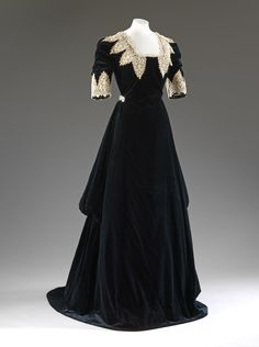 Evening dress of black silk velvet trimmed with white chemical lace in the Van Dyck manner, by John Redfern, c. 1909. The intentionally historical appearance of the gown suggests it may have been made for fancy dress. © Victoria and Albert Museum, London. See: http://collections.vam.ac.uk/item/O362559/evening-dress-john-redfern/