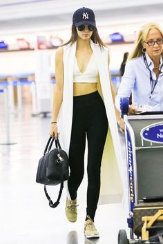 Kendall Jenner shows off her stunning crop top by layering a sleeveless coat atop and finishes the look with a basket ball hat and her signature shades.