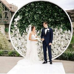circular backdrop adorned with greenery and white hued bloom