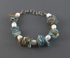 Náramek perly bílé s mušlemi LI474. Náramek je vyroben z ušlechtilé oceli, zdoben bílými sladkovodními perlami a sekanými mušlemi. Barva perel je bílá s přirozenými odlesky, velikost 9-11 mm, tvar oválný s jemnými nedokonalostmi a rýhami. Rozměr mušlí je cca 10-14 mm. Zapínání je na karabinku. Celková délka náramku je 20 cm, zapnou lze na 18 cm, 18,5cm, 19 cm, 19,5 cm a 20 cm  Orientační hmotnost je 19,6 g.  Náramek se hodí k náušnicím SP6241.  Náramek byl vyrobeny v České republice.