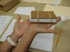 """They also showed us how to make a mini flower press (first picture) using cardboard and index cards. Obviously these would be smaller specimens and the professor suggested putting wax paper between the layers. The rubber bands would be used to secure the """"press""""."""