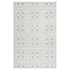Anchor your living room or define a space in your master suite with this hand-tufted wool rug, showcasing a quatrefoil motif in light blue and ivory.