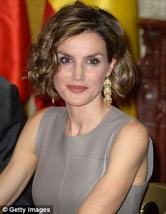 The Spanish royal, 42, looked glamorous  wearing her choppy bob in tight curls and accessorising with gold drop earrings