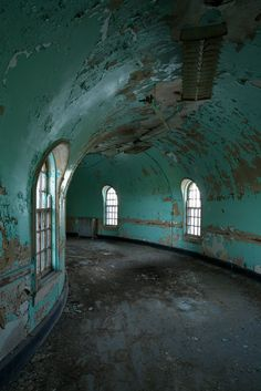 A hallway inside the sandstone wards at Buffalo State Hospital. Kirkbride institutions followed a floor plan of a central building connected to long wings, which are staggered in a linear fashion on either side.