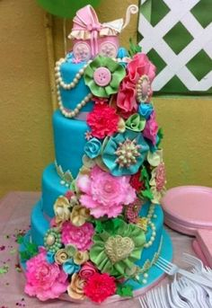 Submitted by Courtney P. and made by Royal Decadence Cakes    Ruffles and flowers and bows, oh my!!    Not only is that some killer cute detailing, I'm also loving the color choices. Apple green, sky blue, fuchsia, and gold make a surprisingly beautiful combination!