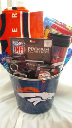 Denver Broncos bucket comes with a Broncos beach towel, 3 in 1 key chain, coasters, playing cards, travel mug and snacks.